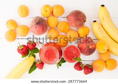 Healthy food. Strawberry banana smoothie with mint in a glass and pitcher on white wooden background. Fresh fruits bananas, peaches and apricots background. Selective focus. Top view - stock photo