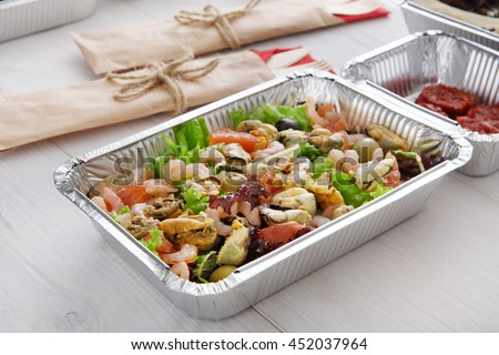 Healthy food take away, diet concept. Organic nutrition. Weight loss dish in foil box. Vegetarian seafood salad with mussels, shrimp, tomatoes, olives and grapefruit closeup - stock photo