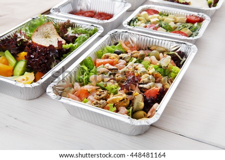 Healthy food take away, diet concept. Organic nutrition. Weight loss dish in foil boxes. Vegetarian seafood salad with mussels, shrimp, tomatoes, olives and grapefruit at white wood - stock photo