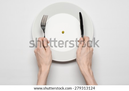 Healthy food theme: hands holding knife and fork on a plate with green peas on a white table top view - stock photo