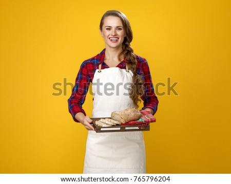 Healthy food to your table. Portrait of happy modern woman cook wearing apron isolated on yellow background showing sliced fresh bread on a tray