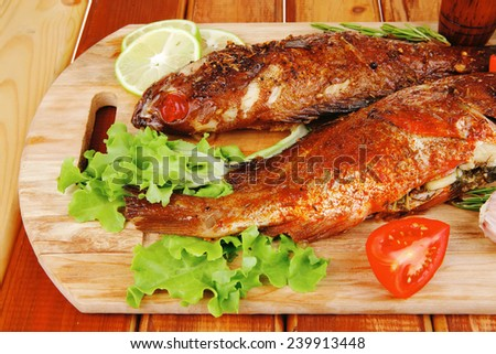 healthy food: two fried sea bass fish served with tomatoes and vegetables on big wooden board over table - stock photo