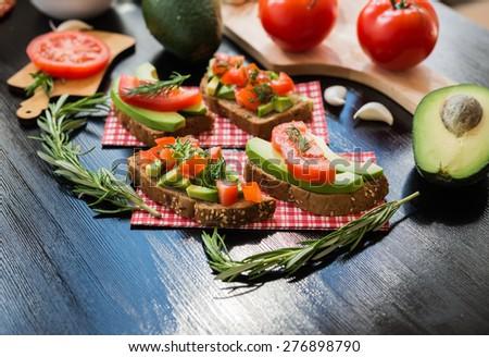Healthy food. Vegan food. Vegetable appetizers. Sandwich : Rye Bread, Avocado, Tomatoes, Dill. - stock photo