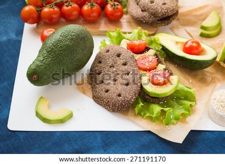 Healthy food. Vegetable appetizers. Sandwich. Rye Bread, Avocado, Lettuce, Cherry Tomatoes  - stock photo