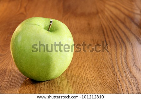 Healthy food: vibrant green granny smith apple on wooden kitchen table with copy space.