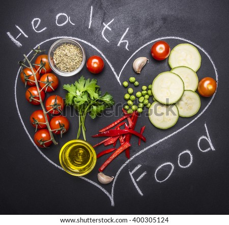 Healthy foods, cooking and vegetarian concept cherry tomatoes, zucchini with parsley, butter and pepper, to draw on a blackboard heart on wooden rustic background top view - stock photo
