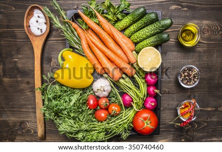 Healthy foods, cooking and vegetarian concept fresh carrots cherry tomatoes, garlic, cucumber, lemon, pepper, radish, wooden spoon salt pepper colored, oil wooden rustic background top view close up - stock photo