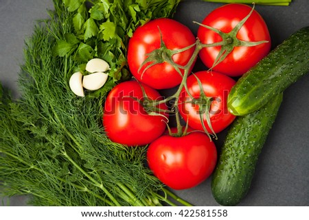 Healthy foods, cooking and vegetarian concept fresh carrots with tomatoes, garlic, cucumbers, dill and parsley on dark background top view. close up - stock photo