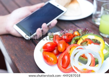 healthy foods, Sweet Peppers or Bell Peppers slice and red tomato on blur hand holding mobile phone background ,Concept for technology and anti oxidant by healty food - stock photo
