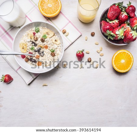 Healthy foods,  vegetarian concept hazelnuts, strawberries and oranges, oatmeal, milk and juice border ,place for text  on wooden rustic background top view close up - stock photo