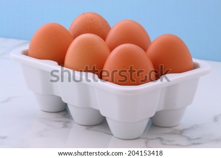 Healthy free range eggs on porcelain crate over vintage carrara marble kitchen station. - stock photo