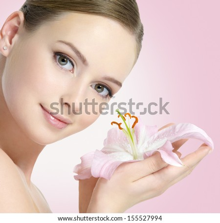 Healthy fresh face of beautiful young woman with lily flower in hands - stock photo