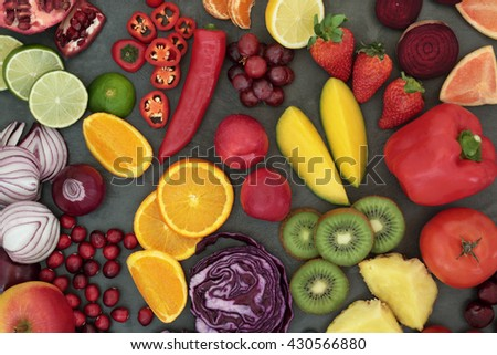 Healthy fresh fruit and vegetable superfood background on slate, high in antioxidants, anthocyanins, vitamins, dietary fiber and minerals. - stock photo