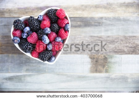 Healthy fresh fruit salad with strawberries, blackberries, blueberries and raspberries. in heart shape bowl. - stock photo