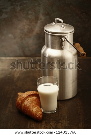 Healthy fresh milk for breakfast in a tall tumbler freshly dispensed from the metal milk can and served with a crisp golden croissant in a rustic kitchen - stock photo