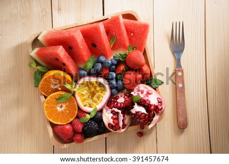 healthy fresh mixed fruits snack on wooden plate - stock photo