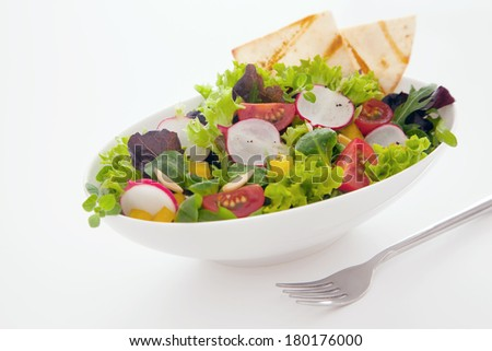 Healthy fresh mixed salad and crisp freshly baked flat bread with leafy green lettuce, radish, sweet pepper amd tomato on a white background