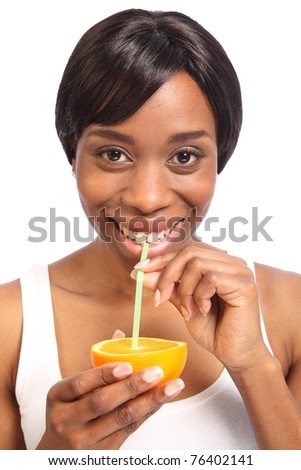 Healthy fresh orange drink using a straw straight from a fruit slice, by beautiful young black woman with a lovely smile. - stock photo