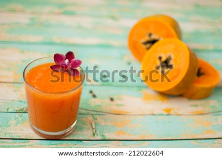 healthy fresh papaya smoothie juice on wooden green boards - stock photo