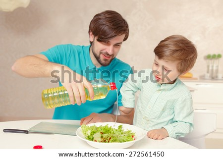 Healthy fresh salad. Young handsome man and his son pouring oil into fresh vegetable salad - stock photo