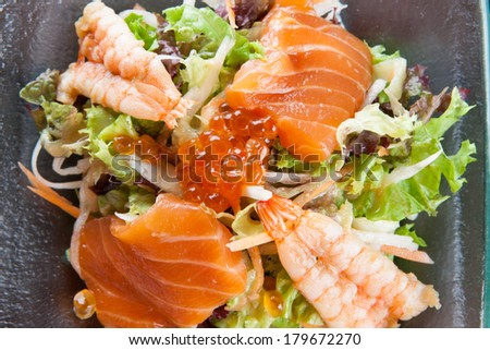 Healthy fresh seafood sashimi salad with a bed of leafy greens and herbs topped with salmon, prawns and fish roe - stock photo