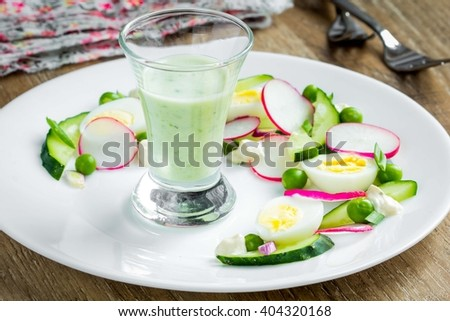 Healthy fresh spring salad with radish, cucumber, eggs, peas, restaurant dish, beautiful presentation with sauce - stock photo