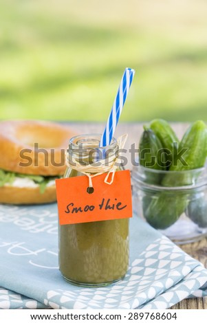 Healthy freshly liquidized green herb and vegetable smoothie with fresh rocket or arugula leaves and cucumbers in a jar on a napkin on a rustic table in the garden - stock photo