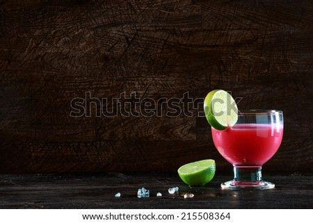 Healthy fruit cocktail made with mixed berries blended with alcohol garnished with a slice of fresh lime standing on a bar counter against a dark background with copyspace - stock photo