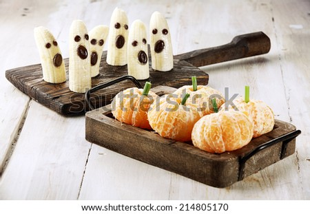 Healthy Fruit Halloween Treats made into Banana Ghosts and Clementine Orange Pumpkins - stock photo