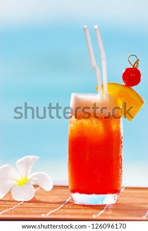 Healthy fruit punch. Healthy fruit punch. Sea on background color. Decorate with orange cherry. And frangipani flowers. - stock photo