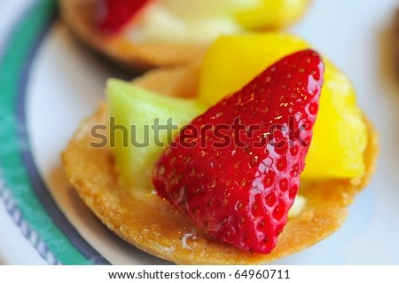 Healthy fruit tarts prepared with different colored cut fruits such as strawberries and honey dew.