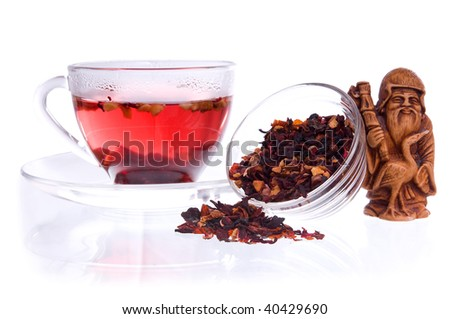 Healthy fruit tea in a transparent cup and saucers with dry fruit tea, and idol of prosperity statuette - stock photo