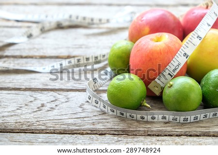 Healthy Fruit with measuring tape on wooden top , for lose weight ,Diet, Healthy lifestyle concept - stock photo