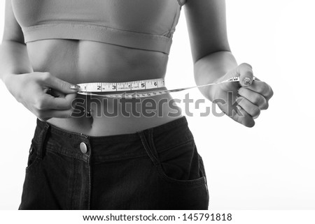 healthy girl measuring herself with a tape measure around her waist - stock photo