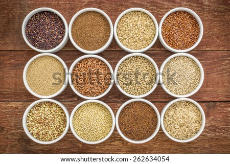 healthy, gluten free grains collection (quinoa, brown rice, millet, amaranth, teff, buckwheat, sorghum) , top view of small round bowls against rustic wood - stock photo