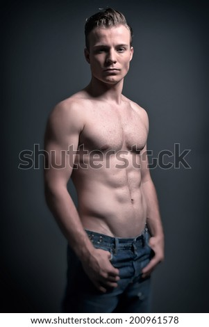 Healthy good looking young muscled fitness man wearing blue jeans. Studio shot.