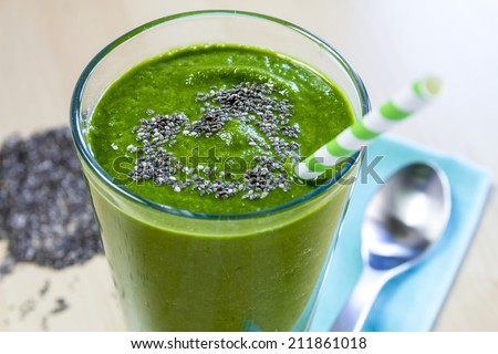 Healthy green fresh fruit and vegetable juice smoothie with blue striped straw and chia seeds heart garnish - stock photo