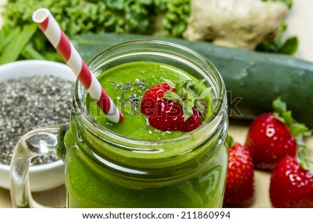 Healthy green juice smoothie surrounded by whole fruits, vegetables and chia seeds with fresh strawberry garnish and red swirl straw - stock photo