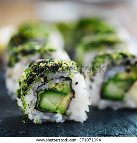 healthy green kale and avocado sushi roll on slate close up - stock photo