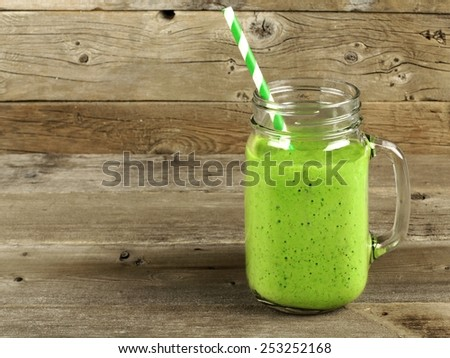 Healthy green smoothie in a mason jar mug on old wood - stock photo
