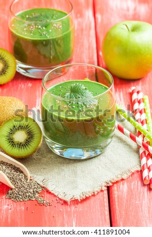 Healthy green smoothie made from  kiwi, bananas and apples in a glass with straws on red wooden table. - stock photo