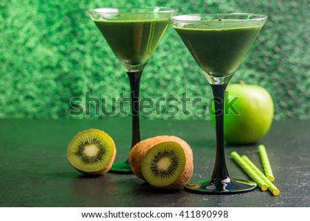 Healthy green smoothie made from  kiwi, bananas and apples in martini glasses on black table. - stock photo