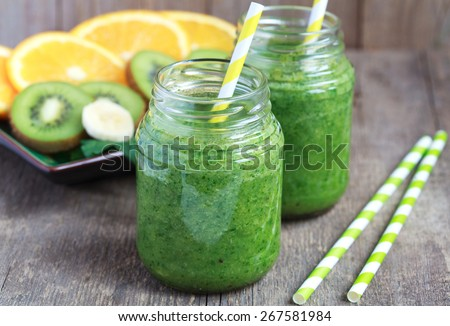 Healthy green smoothie made from spinach, kiwi, bananas and oranges in a jar with yellow straws on a wooden table, selective focus - stock photo