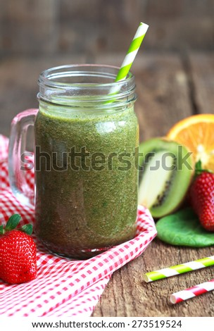 Healthy green smoothie made from spinach, kiwi, strawberries and oranges in a jar with green straw on a wooden table, selective focus - stock photo