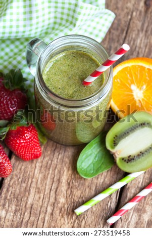 Healthy green smoothie made from spinach, kiwi, strawberries and oranges in a jar with red straw on a wooden table, selective focus - stock photo