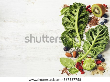 Healthy green smoothie or salad ingredients on white - superfoods, detox, diet, health or vegetarian food concept. Background layout with free text space. - stock photo