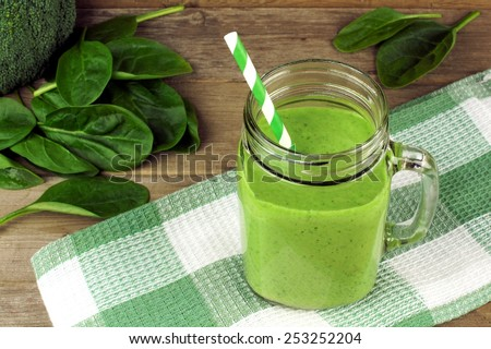 Healthy green smoothie with spinach in a jar mug with checkered cloth against wood - stock photo
