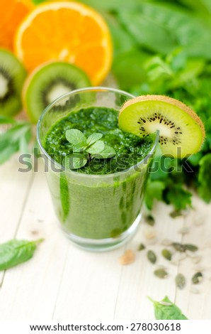 Healthy green smoothie with spinach, kiwi and orange and mobile phone with image on wooden light retro table. Top View