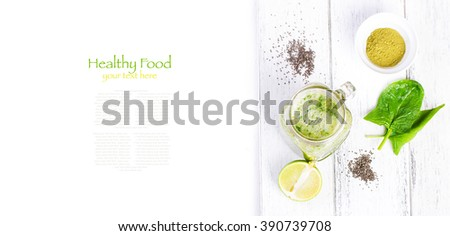 Healthy green smoothie with spinach, kiwi, banana, chia seeds, lime and green tea matcha in a glass jar on a white wooden background with copy space, top view - stock photo