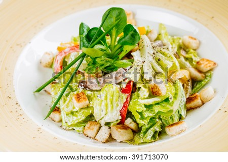 Healthy Grilled Chicken Caesar salad with chicken and greens  on dark rustic table - stock photo